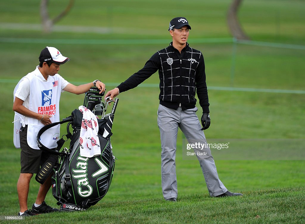Ryo Ishikawa of Japan selects a club on the ninth hole during the first round of the Farmers Insurance Open at Torrey Pines Golf Course on January 24, 2013 in La Jolla, California.