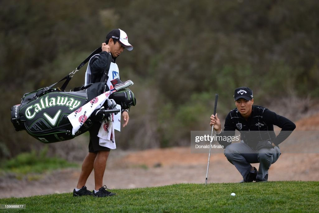 Ryo Ishikawa (R) of Japan studies his positioning during the First Round at the Farmers Insurance Open at Torrey Pines Golf Course on January 24, 2013 in La Jolla, California.
