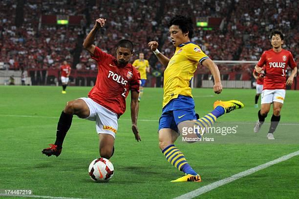 Ryo Miyaichi of Arsenal and Keisuke Tsuboi of Urawa Red Diamonds compete for the ball during the preseason friendly match between Urawa Red Diamonds...