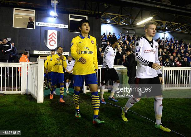 Ryo Miyaichi of Arsenal and Tom Richards of Fulham walk out to the pitch before the match between Fulham U21 and Arsenal U21 in the U21 League Cup on...
