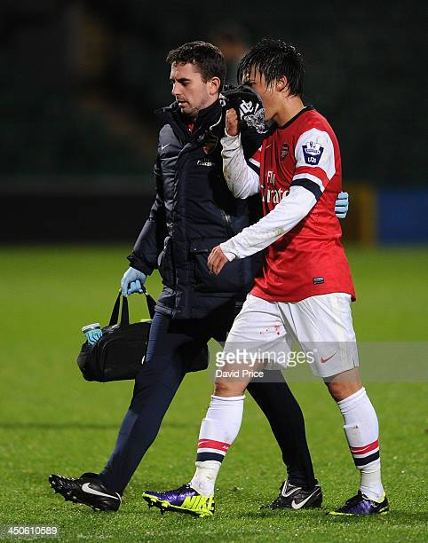 Ryo Miyaichi of Arsenal is escorted from the pitch by Arsenal Physio Alastair Thrush during the match Norwich City U21 against Arsenal U21 at Carrow...