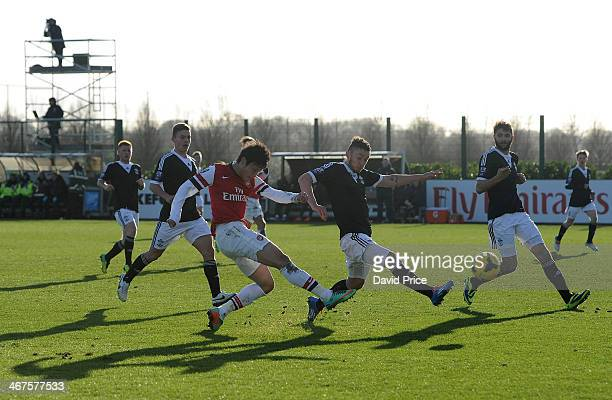 Ryo Miyaichi of Arsenal shoots under pressure from Matt Young of Southampton during the match between Arsenal U21 and Southampton U21 in the Barclays...