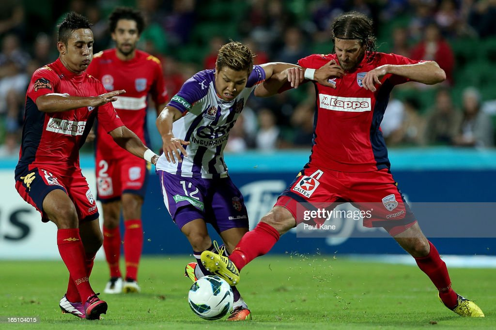 Ryo Nagai of the Glory contests for the ball against Jake Barker-Daish and Jon McKain of Adelaide during the round twenty seven A-League match between Perth Glory and Adelaide United at nib Stadium on March 30, 2013 in Perth, Australia.