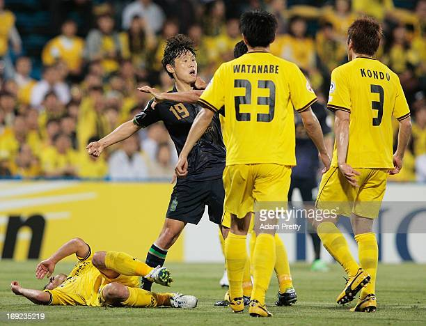 Ryoichi Kurisawa of Kashiwa is knocked to the fground by Park Wonjae of Jeonbuk during the AFC Champions League round of 16 match between Kashiwa...