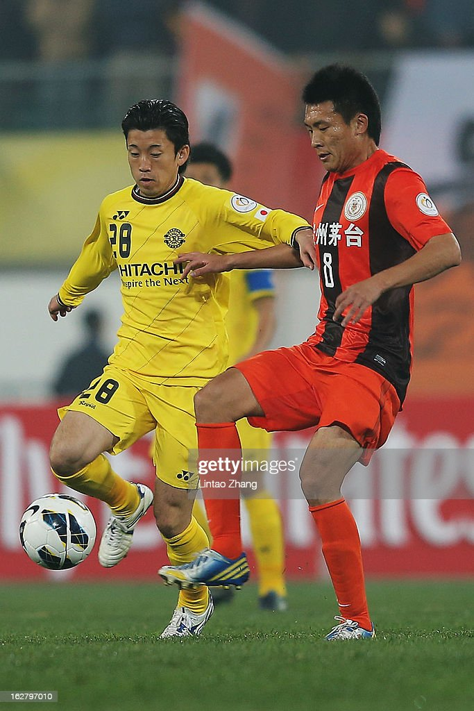 Ryoichi Kurisawa (C) of Kashiwa Reysol controls the ball with Li Chunyu of Guizhou Renhe during the AFC Champions League match between Guizhou Renhe and Kashiwa Reysol at Olympic Sports Center on February 27, 2013 in Guiyang, China.