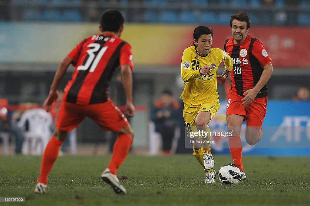 Ryoichi Kurisawa (C) of Kashiwa Reysol controls the ball with Zlatan Muslimovic (R) of Guizhou Renhe during the AFC Champions League match between Guizhou Renhe and Kashiwa Reysol at Olympic Sports Center on February 27, 2013 in Guiyang, China.