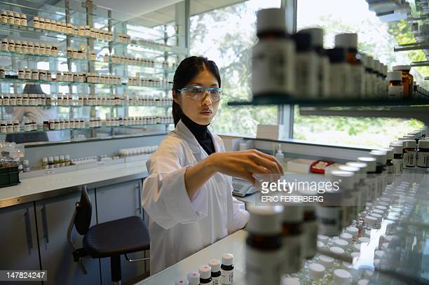 Ryoko Akatsu a student from Japan melts fragrances and oils in a laboratory at the Givaudan Perfumery School on July 4 2012 in Argenteuil northern...