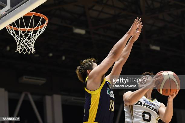 Ryoma Hashimoto of the SeaHorse Mikawa shoots while under pressure from Seiji Ikaruga of the Tochigi Brex during the BLeague game between Tochigi...