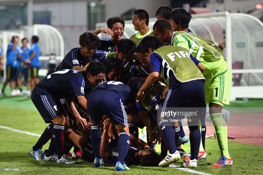 Ryoma Watanabe (C, bottom) of Japan celebrates his team's second goal with team mates during the FIFA U-17 World Cup UAE 2013 Group D match between Japan and Tunisia at Sharjah Stadium on October 24, 2013 in Sharjah, United Arab Emirates.