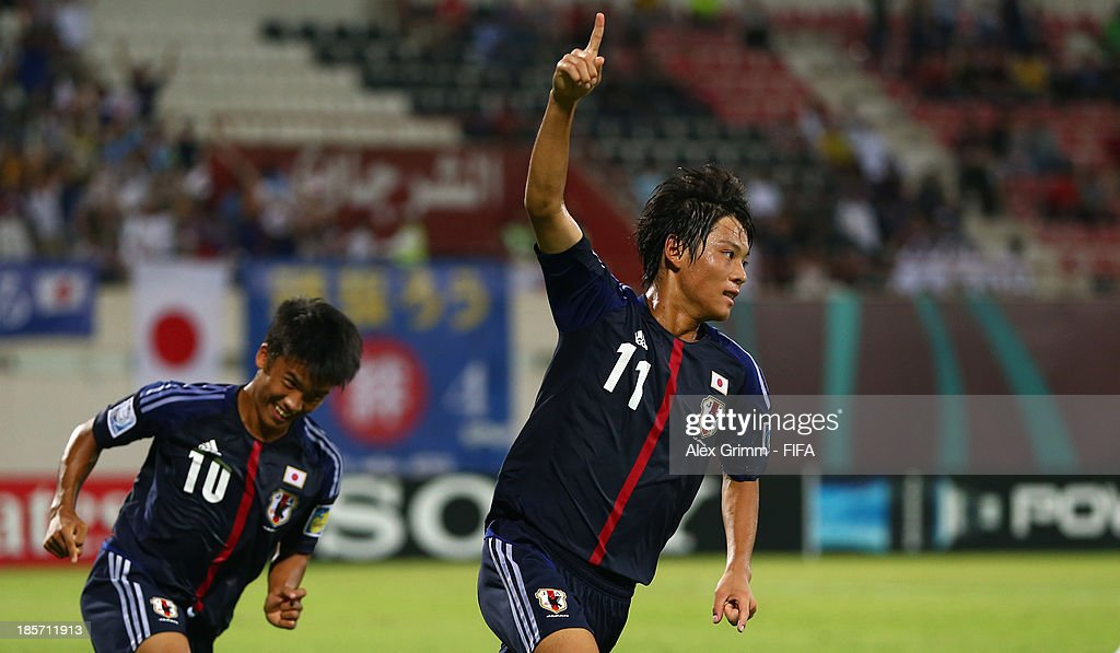 Ryoma Watanabe of Japan celebrates his team's second goal with team mate Takuma Mizutani during the FIFA U-17 World Cup UAE 2013 Group D match between Japan and Tunisia at Sharjah Stadium on October 24, 2013 in Sharjah, United Arab Emirates.