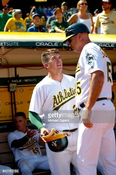 Ryon Healy and Acting Third Base Coach Steve Scarsone of the Oakland Athletics talk in the dugout during the game against the Kansas City Royals at...