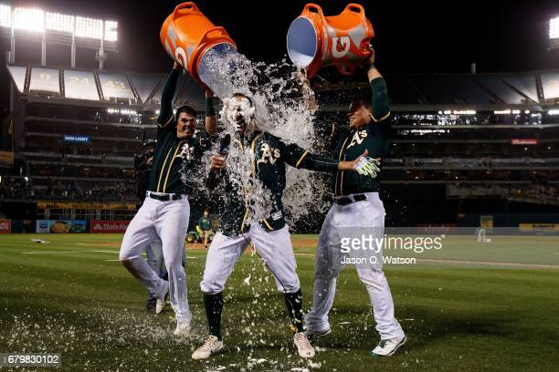 Ryon Healy of the Oakland Athletics and Bruce Maxwell pour water on Adam Rosales after hit he a tworun walk off single against the Detroit Tigers...