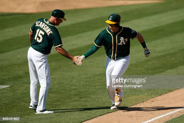 Ryon Healy of the Oakland Athletics celebrates with third base coach Steve Scarsone after hitting a tworun home run in the seventh inning against the...