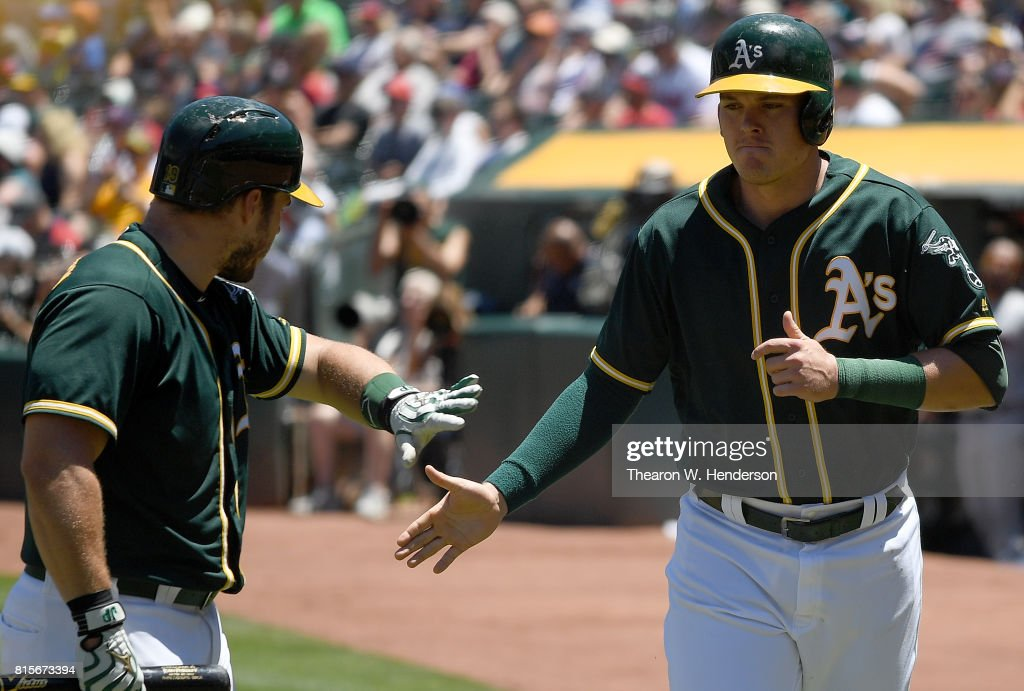 Ryon Healy #25 of the Oakland Athletics (R) is congratulated by Josh Phegley #19 (L) after Healy scored against the Cleveland Indians in the bottom of the first inning at Oakland Alameda Coliseum on July 16, 2017 in Oakland, California.