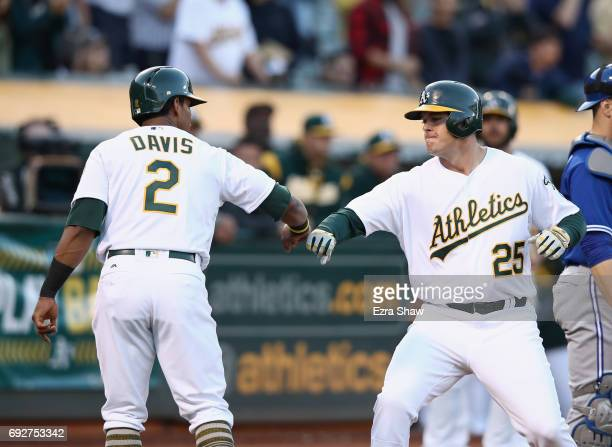 Ryon Healy of the Oakland Athletics is congratulated by Khris Davis after he hit a threerun home run in the second inning against the Toronto Blue...