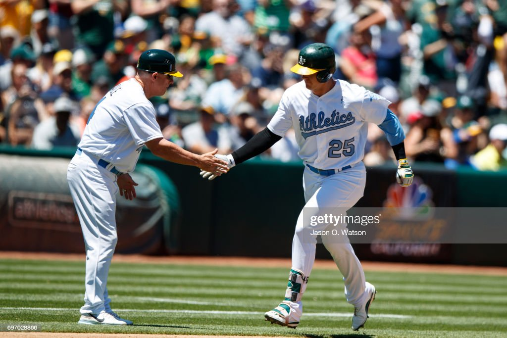 Ryon Healy #25 of the Oakland Athletics is congratulated by third base coach Chip Hale #4 after hitting a home run against the New York Yankees during the second inning at the Oakland Coliseum on June 17, 2017 in Oakland, California. Players and umpires are wearing blue to celebrate Father's Day weekend and support prostrate cancer awareness.