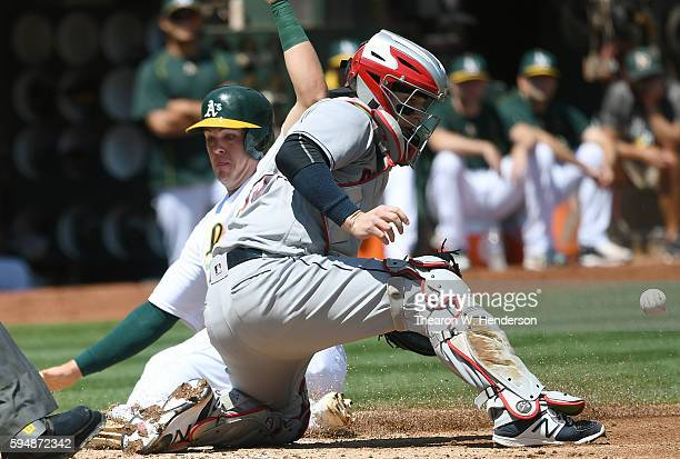 Ryon Healy of the Oakland Athletics slides in safe at home beating the throw to catcher Roberto Perez of the Cleveland Indians in the bottom of the...