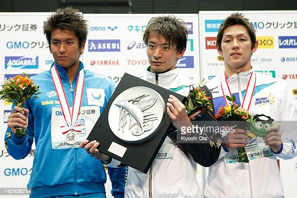 Ryosuke Irie celebrates after winning the Men's 100m Backstroke final with Junya Koga and Yuki Shirai at an award ceremony during day three of the...