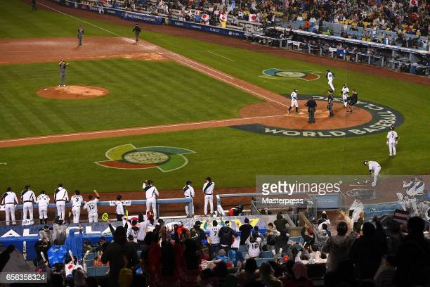 Ryosuke Kikuchi of Japan rounds the bases after a gametying home run with teammates in the six inning during the Game 2 of the Championship Round of...