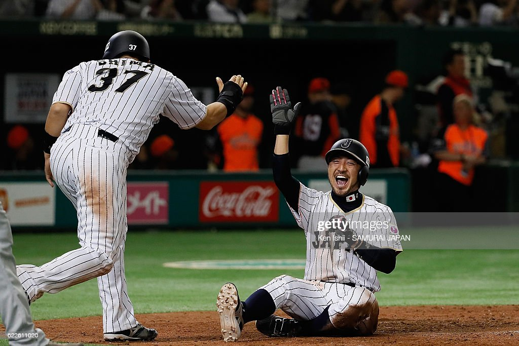 Ryosuke Kikuchi #4 of Japan slides safely into the home base after Hayato Sakamoto #6 of Japan hits three-run double in the fifth inning during the international friendly match between Japan and Netherlands at the Tokyo Dome on November 12, 2016 in Tokyo, Japan.