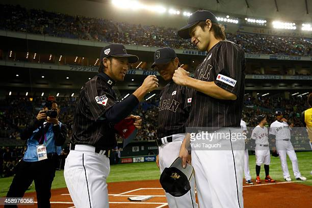 Ryosuke Kikuchi of Samurai Japan is greeted by teammate Yuki Yanagita during player introductions before the game against the MLB AllStars at the...