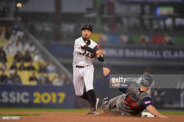 Ryosuke Kikuchi of team Japan makes the pivot to first base as a safe Buster Posey of team United States slides into second in the third inning...