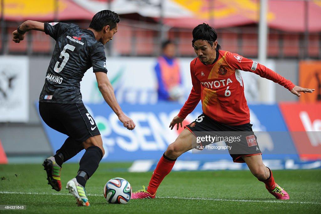 Ryosuke Tone (R) of Nagoya Grampus challenges Tomoaki Makino of Urawa Red Diamonds during the J. League match between Nagoya Grampus and Urawa Red Diamonds at the Toyota Stadium on April 12, 2014 in Toyota, Japan.