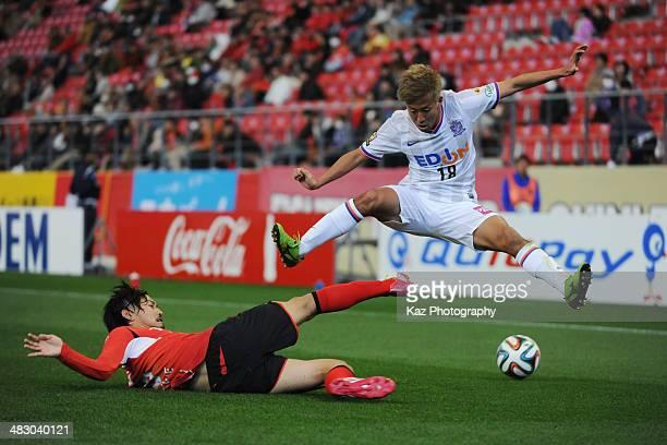 Ryosuke Tone of Nagoya Grampus tackles while Yoshifumi Kashima of Sanfrecce Hiroshima jumps to avoid the colision during the J League match between...