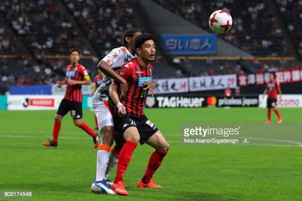 Ryota Hayasaka of Consadole Sapporo controls the ball under pressure of Kanu of Shimizu SPulse during the JLeague J1 match between Consadole Sapporo...