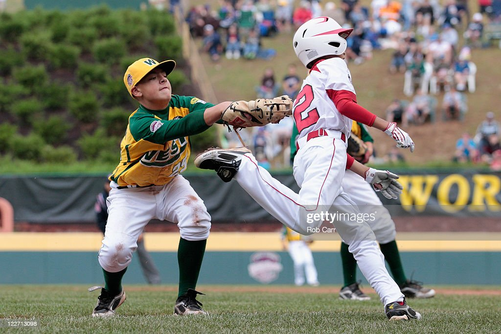 Ryota Matsushita #2 of the Japan team from Hamamatsu City, Japan avoids the tag of first baseman Nick Pratto #25 of the West team from Huntington Beach, California for an infield single during the fourth inning of the Little League World Series championship game on August 28, 2011 in South Williamsport, Pennsylvania. The West team defeated the team from Japan 2-1.