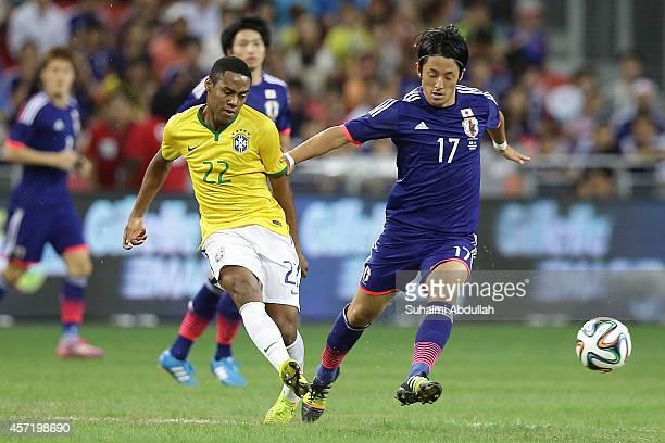 Ryota Morioka of Japan and Elias Mendes Trindade of Brazil challenge for the ball during the international friendly match between Japan and Brazil at...