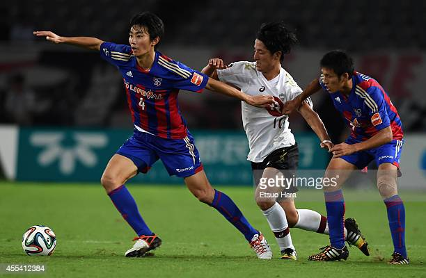 Ryota Morioka of Vissel Kobe competes for the ball against Hideto Takahashi and Takuji Yonemoto of FC Tokyo during the JLeague match between FC Tokyo...