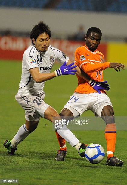 Ryota Moriwaki of Sanfrecce Hiroshima competes for a ball with Fred Benson of Shandong Luneng during the AFC Champions League between Shandong Luneng...