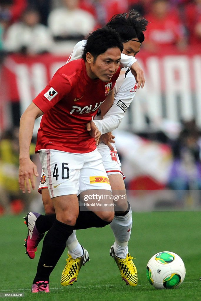 Ryota Moriwaki of Urawa Red Diamonds and <a gi-track='captionPersonalityLinkClicked' href=/galleries/search?phrase=Jungo+Fujimoto&family=editorial&specificpeople=2168009 ng-click='$event.stopPropagation()'>Jungo Fujimoto</a> of Nagoya Grampus compete for the ball during the J.League match between Urawa Red Diamonds and Nagoya Grampus at Saitama Stadium on March 9, 2013 in Saitama, Japan.