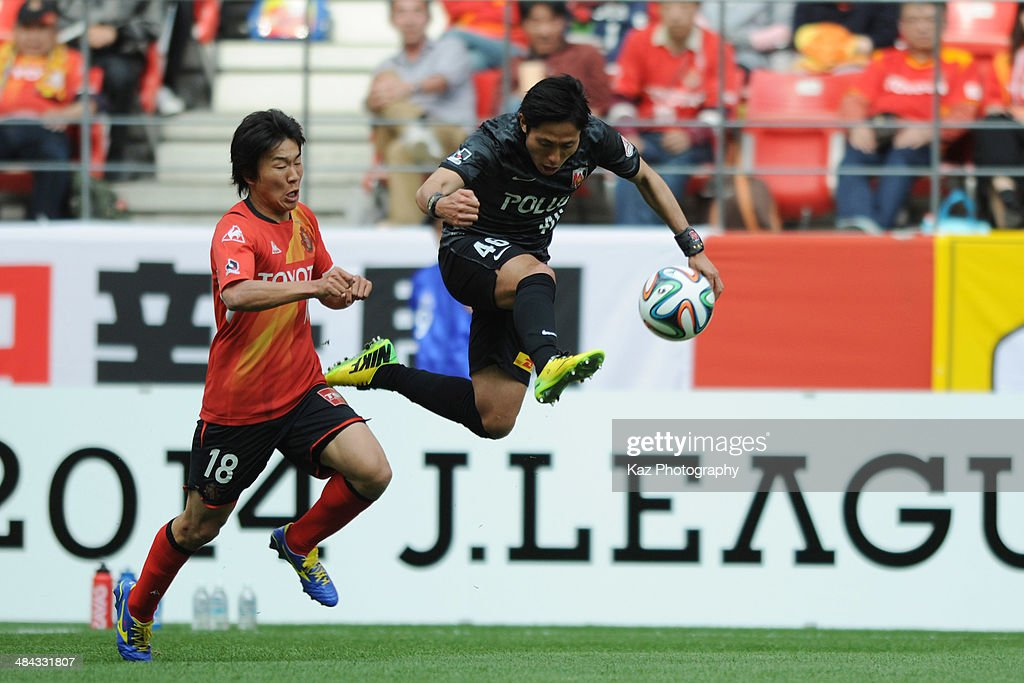 Ryota Moriwaki of Urawa Red Diamonds beats <a gi-track='captionPersonalityLinkClicked' href=/galleries/search?phrase=Kensuke+Nagai&family=editorial&specificpeople=6548859 ng-click='$event.stopPropagation()'>Kensuke Nagai</a> of Nagoya Grampus during the J. League match between Nagoya Grampus and Urawa Red Diamonds at the Toyota Stadium on April 12, 2014 in Toyota, Japan.
