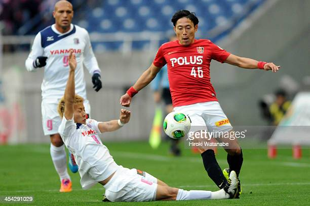 Ryota Moriwaki of Urawa Red Diamonds is tackled by Yoichiro Kakitani of Cerezo Osaka during the JLeague match between Urawa Red Diamonds and Cerezo...