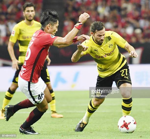 Ryota Moriwaki of Urawa Reds and Gonzalo Castro of Borussia Dortmund vie for the ball during the first half of an international friendly at Saitama...