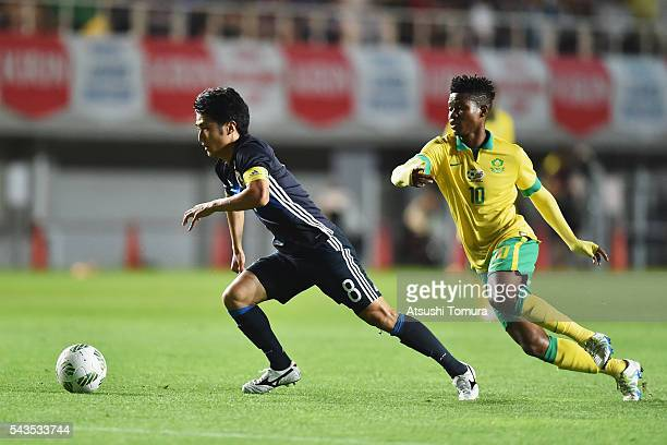 Ryota Oshima of Japan controls the ball under pressure of Menzi Masuku of South Africa during the U23 international friendly match between Japan and...