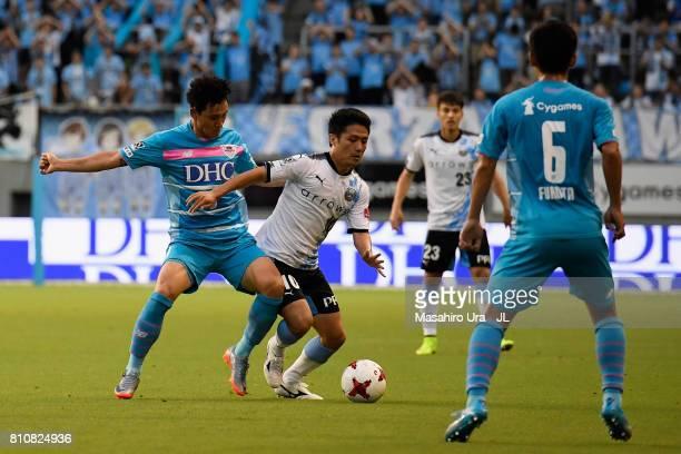 Ryota Oshima of Kawasaki Frontale and Cho Dong Geon of Sagan Tosu compete for the ball during the JLeague J1 match between Sagan Tosu and Kawasaki...
