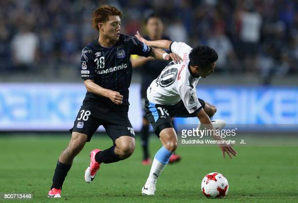 Ryota Oshima of Kawasaki Frontale controls the ball under pressure of Ritsu Doan of Gamba Osaka during the JLeague J1 match between Gamba Osaka and...