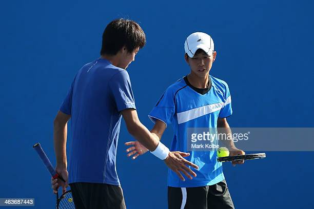 Ryotero Matsumura and Makoto Ochi of Japan in action against Omar Jasika of Australia in action in his first round junior boys' doubles match against...