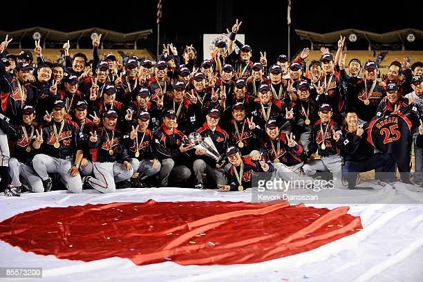 Ryozo Kato Japanese baseball commissioner holds the championship trophy as he poses with team Japan after defeating Korea during the finals of the...