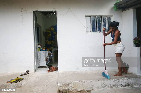 Ryquelme Kauan who was born with microcephaly attempts to crawl toward his mother Avila as she cleans before the start of his one year birthday party...