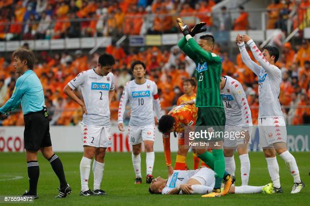 Ryuji Kawai of Consadole Sapporo liess injured while his team mates send signs to the bench during the JLeague J1 match between Shimizu SPulse and...
