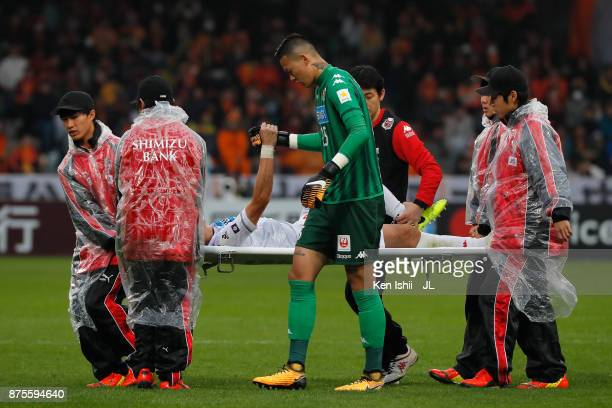 Ryuji Kawai of Consadole Sapporo shakes hands with his team mate Gu Sung Yun while stretched off during the JLeague J1 match between Shimizu SPulse...