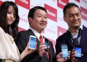 Ryuji Yamada president and chief executive officer of NTT DoCoMo Inc center poses with Japanese actor Ken Watanabe right and actress Maki Horikita...