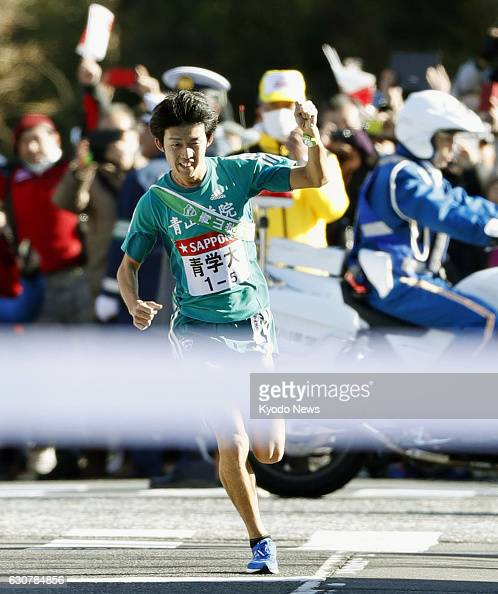 Ryusuke Sadanaga of Aoyama Gakuin University pumps his fist as he crosses the finish line for the first half of the twoday TokyoHakone collegiate...