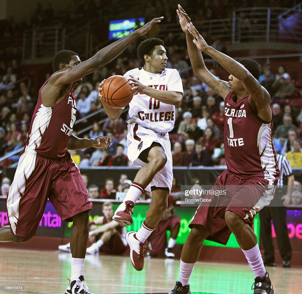 BC's 5'9' freshman guard Jordan Daniels splits the defense of Florida State's Bernard James left and Xavier Gibson right in the first half Boston...
