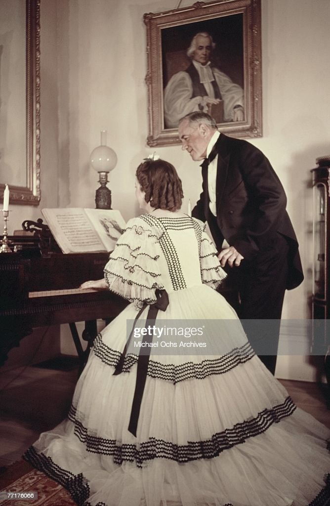 MID 1930's A Southern Belle plays the piano in the drawing room during a recreation of pre Civil War life on a plantation circa mid 1930's in the...