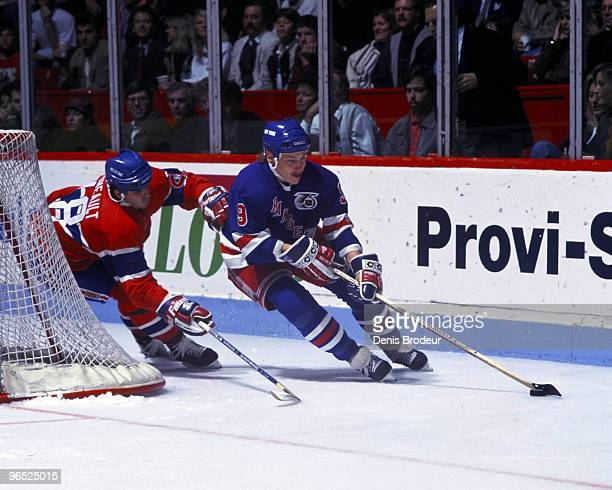 MONTREAL 1990's Adam Graves of the New York Rangers carries the puck behind the net against JeanJacques Daigneault of the Montreal Canadiens in the...